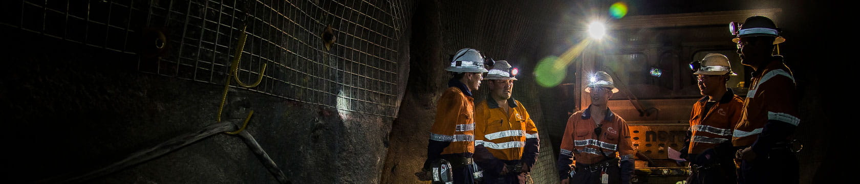 5 male workers underground with hard hats and lights